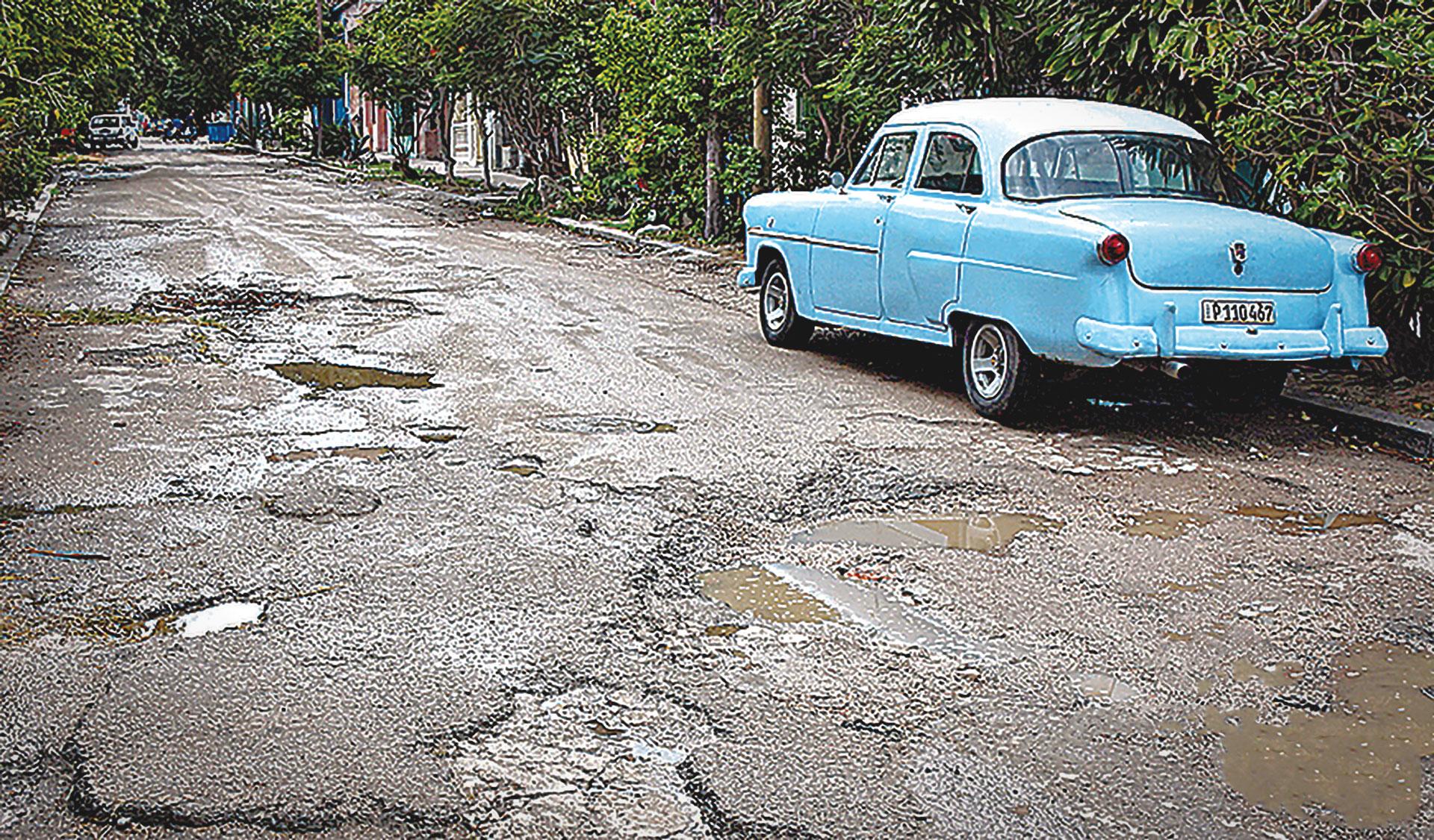 Auto parqueado a la orilla de una calle llena de baches